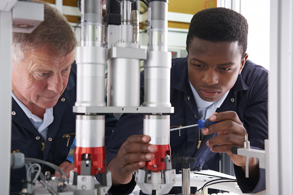 Two men fixing a piece of manufacturing equipment