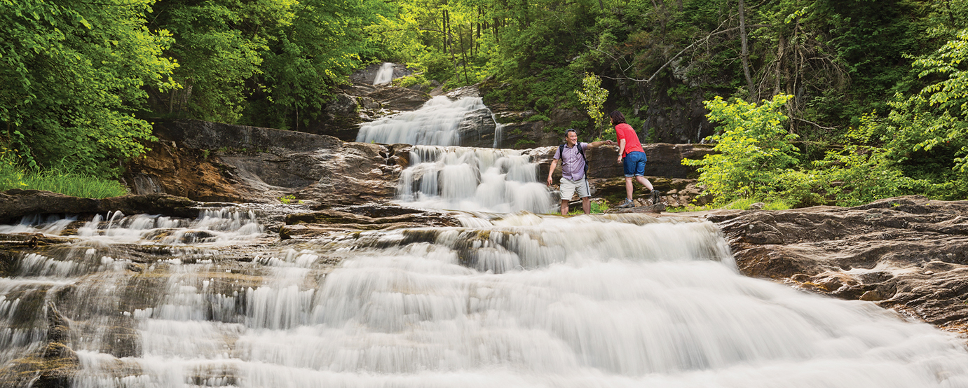 Couple hiking by a waterfall