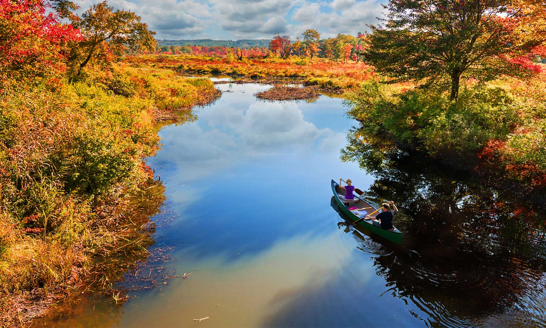 Two people on a canoe, on a river, surrounded by fall foliage