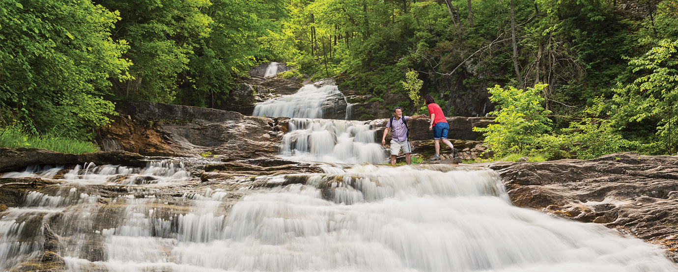 Two people hiking over a river at Kent Falls