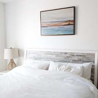 Bed with white sheets and a picture of the ocean hanging on the wall over the bed.