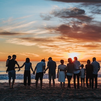 People holding hands on a beach facing the sunset