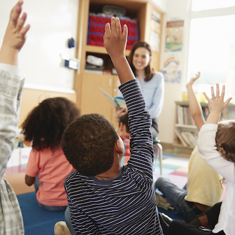 A teacher with children raising their hands