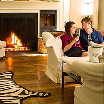 Couple enjoying wine in a room in front of a fire