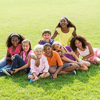 A group of children sitting in the grass