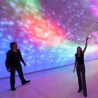 Two people walking in a hallway looking at light artwork