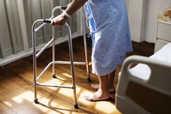 A person in a hospital gown using a walker