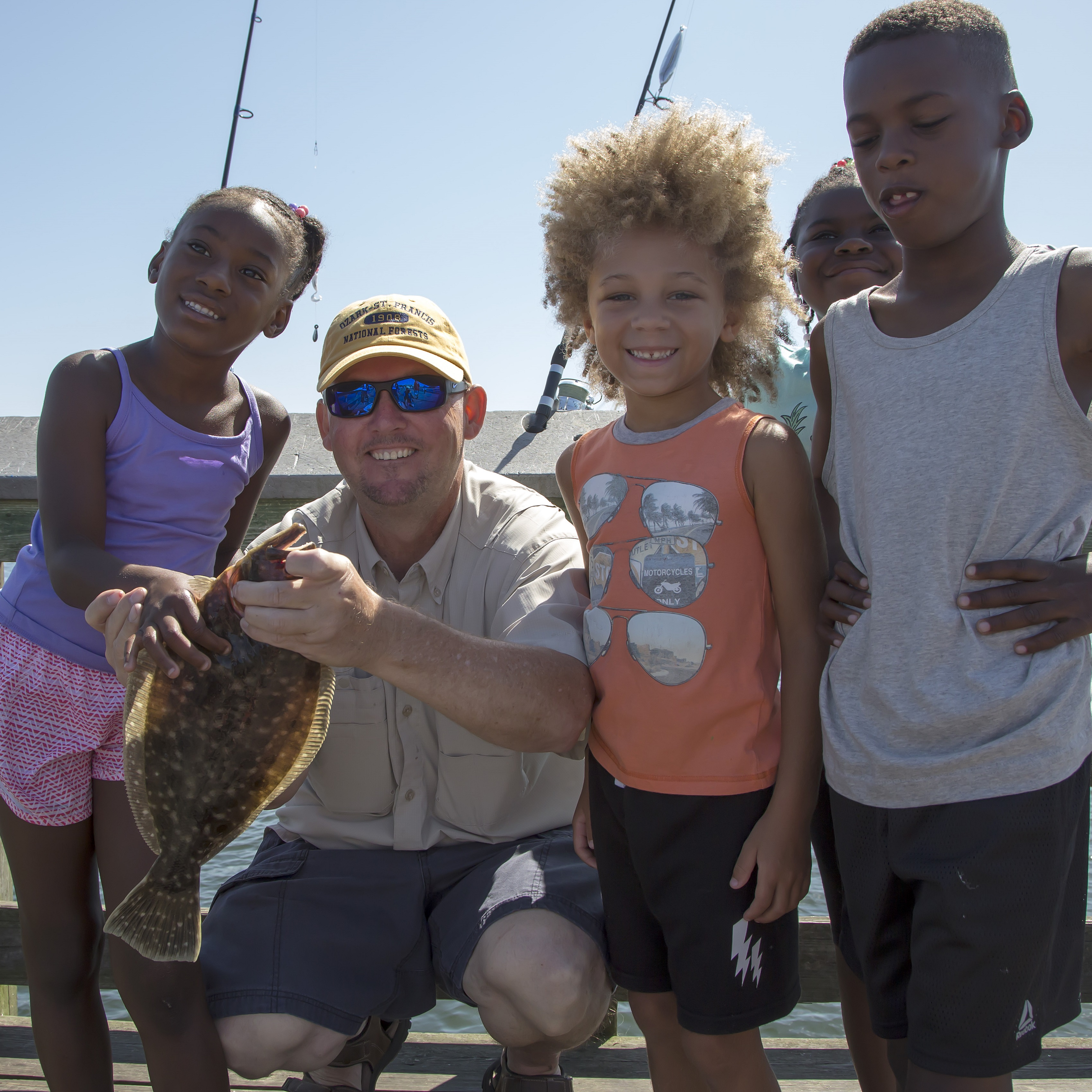 New anglers catching a fluke with a certified CARE fishing instructor.