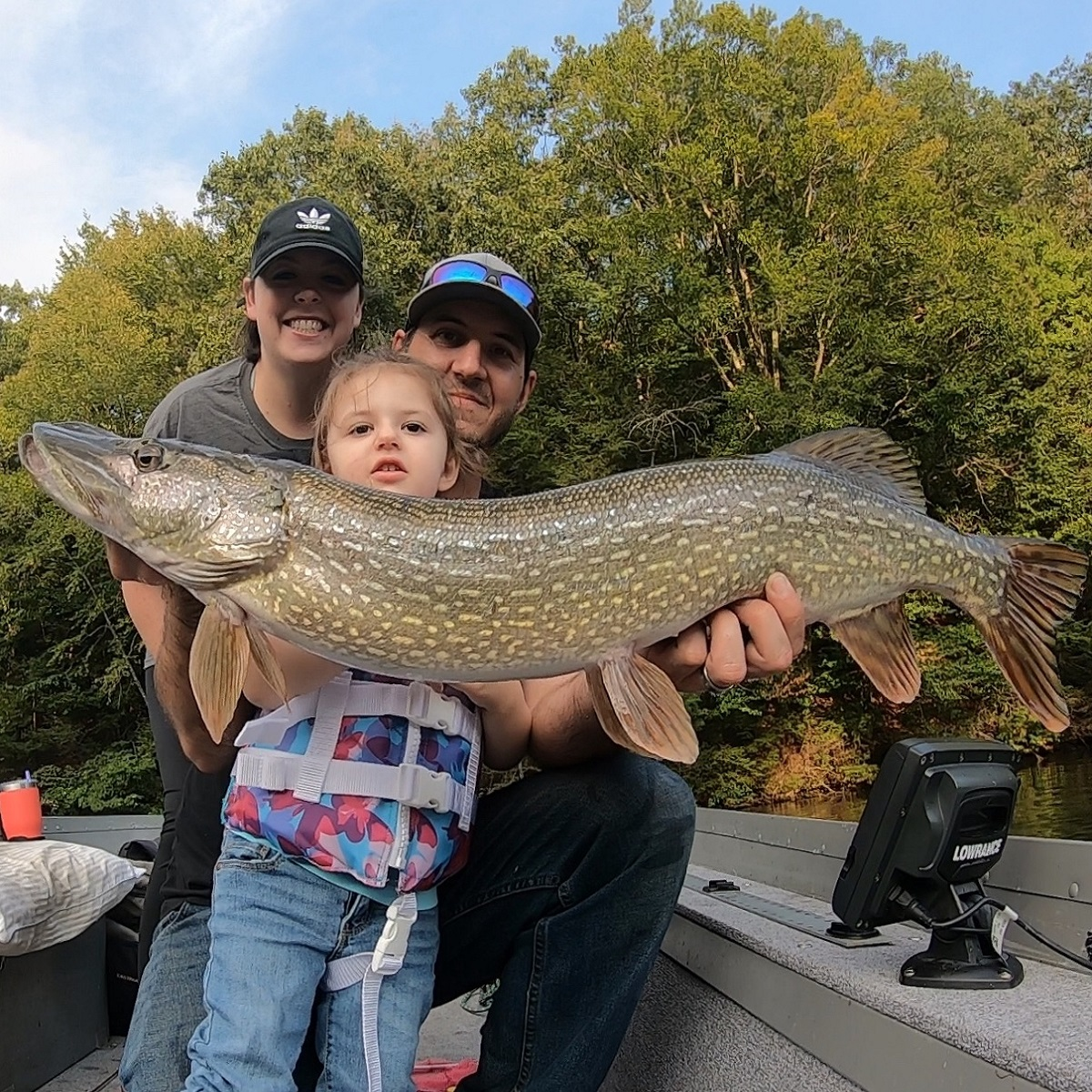 Family with a big northern pike.