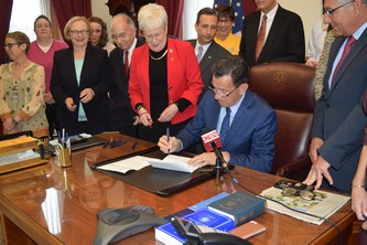 Governor Malloy signs legislation at his desk