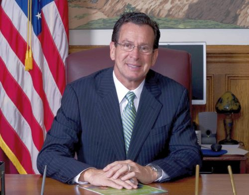 Governor Dannel P. Malloy Sitting at a Desk with an American Flag in the Background