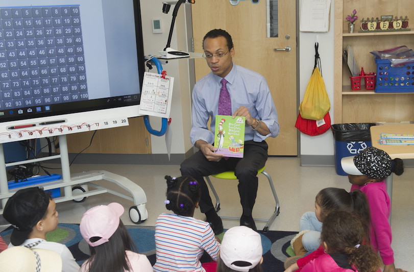 Treasurer Shawn T. Wooden reading to a classroom.