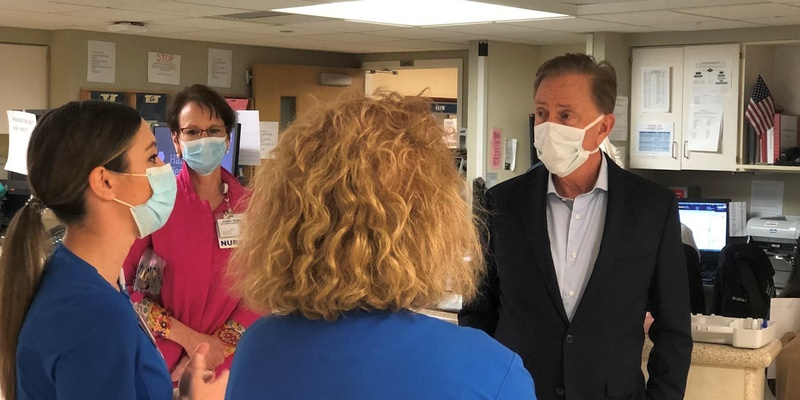 Governor Lamont in a face mask speaking with nurses