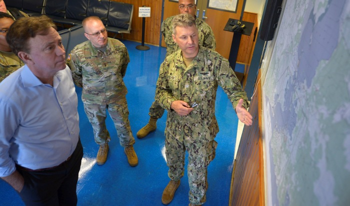 GUANTANAMO BAY, Cuba (Dec. 27, 2019) Capt. John Fisher, commanding officer of Naval Station Guantanamo Bay (NSGB), right, briefs Governor Ned Lamont, left, and Maj. Gen. Francis Evon, Jr., adjutant general of the Connecticut National Guard, center, about the location of NSGB in the U.S. Southern Command area of operations. NSGB is the forward, ready, and irreplaceable sea power platform in the Caribbean, and has supported the Navy's most advanced ships for more than a century. (Credit: U.S. Navy photo by Mass Communication Specialist 2nd Class Kevin J. Steinberg/RELEASED)