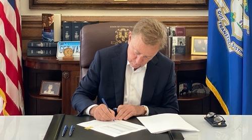 Governor Lamont at his desk signing legislation