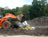 picture of a front loader at a farm moving food scraps