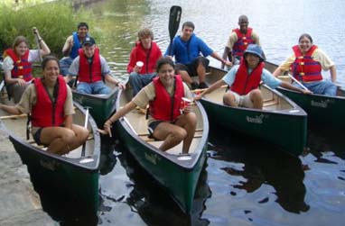 Students canoeing on a pond.