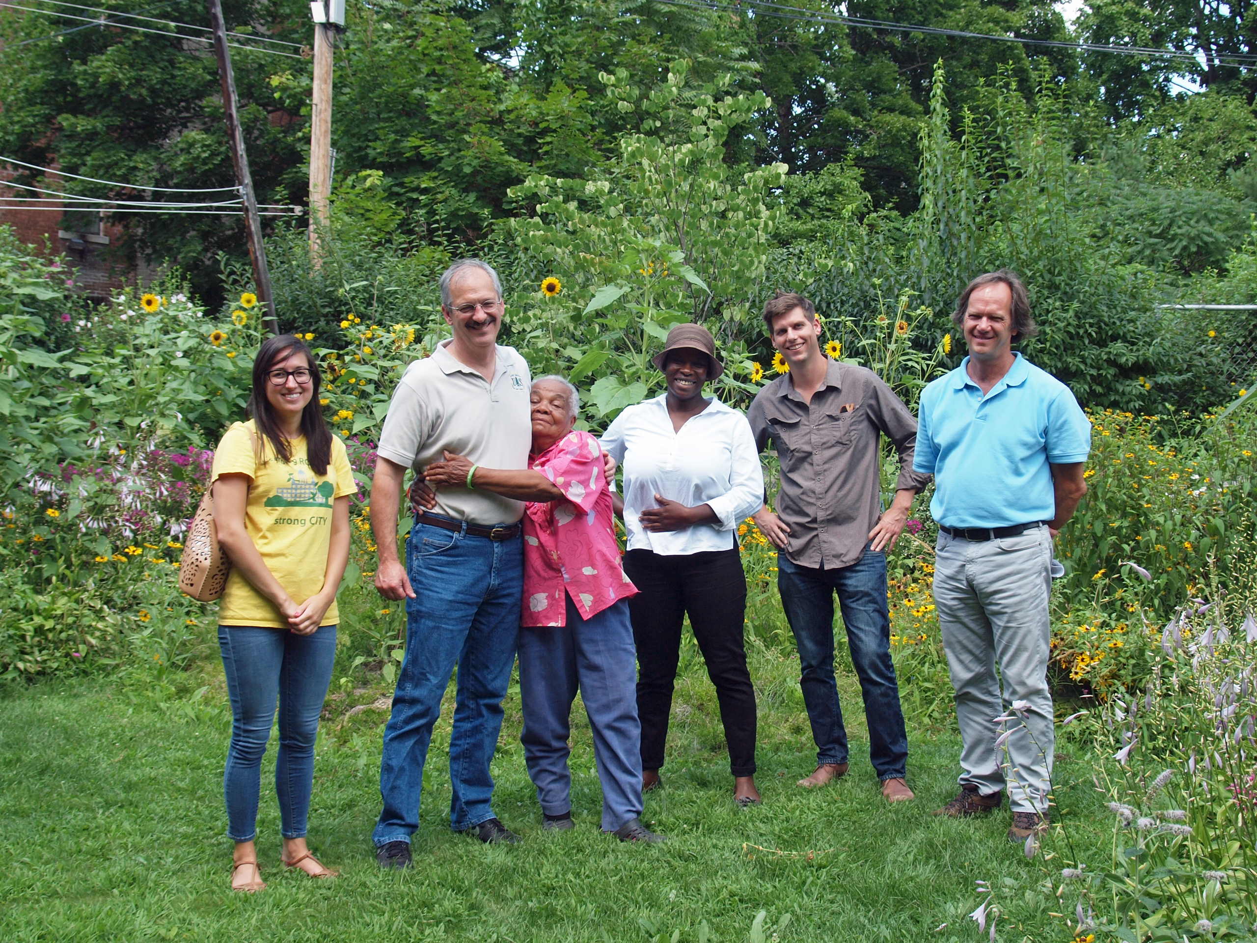 Members from Knox and from the US Forest Service pose with a Hartford resident.  Through a grant, Knox had led an effort to promote tree planting and maintenance on private properties, including back yards.