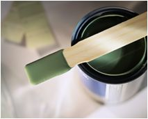 Image of paint can with green paint and stirring stick