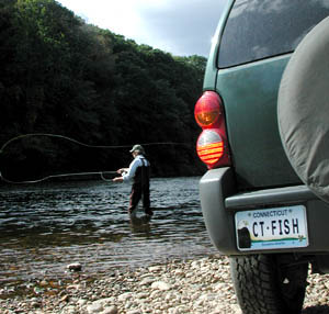 Flyfisherman near vehicle with simulated Wildlife License Plate.