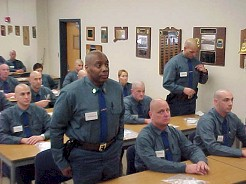 Recruit standing at attention while being addressed in the classroom