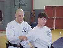 Recruits practicing handcuffing and escorting techniques