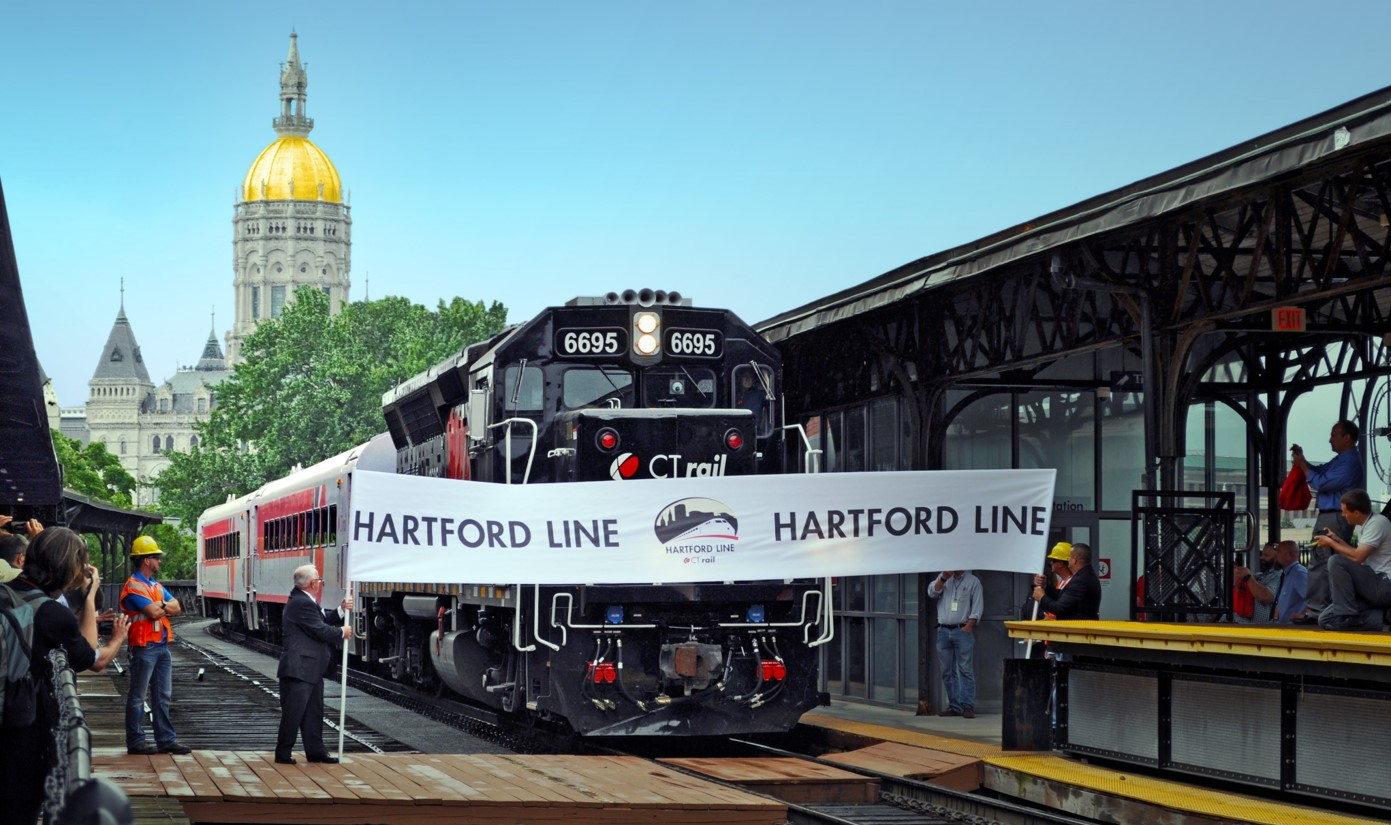 photo of a Hartford Line train moving through the opening day banner at Union Station in Hartford, Connecticut