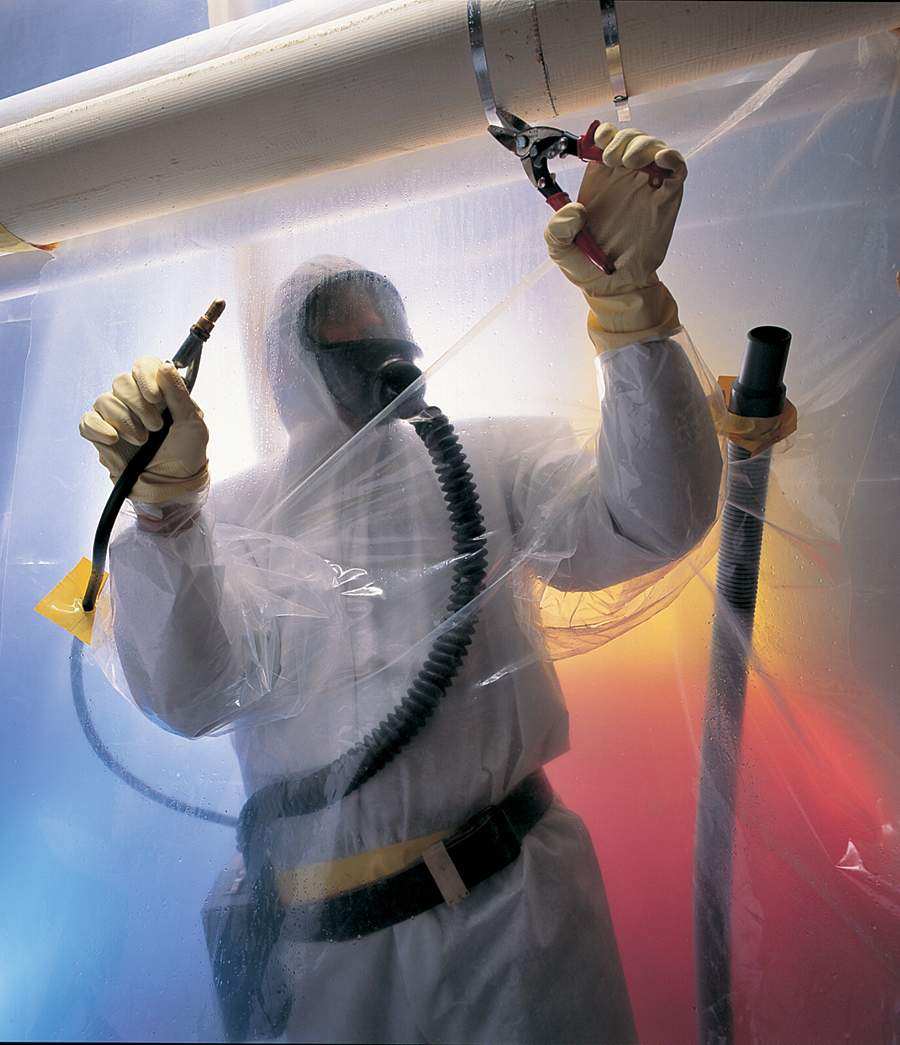Person in a hazardous material protective suit working on a pipe