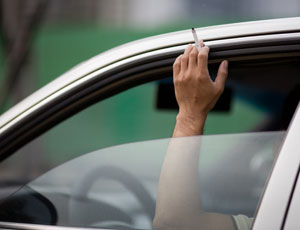 hand in car window with cigarette